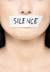 woman with word 'silence' taped over her mouth