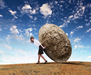 Woman rolling a giant stone